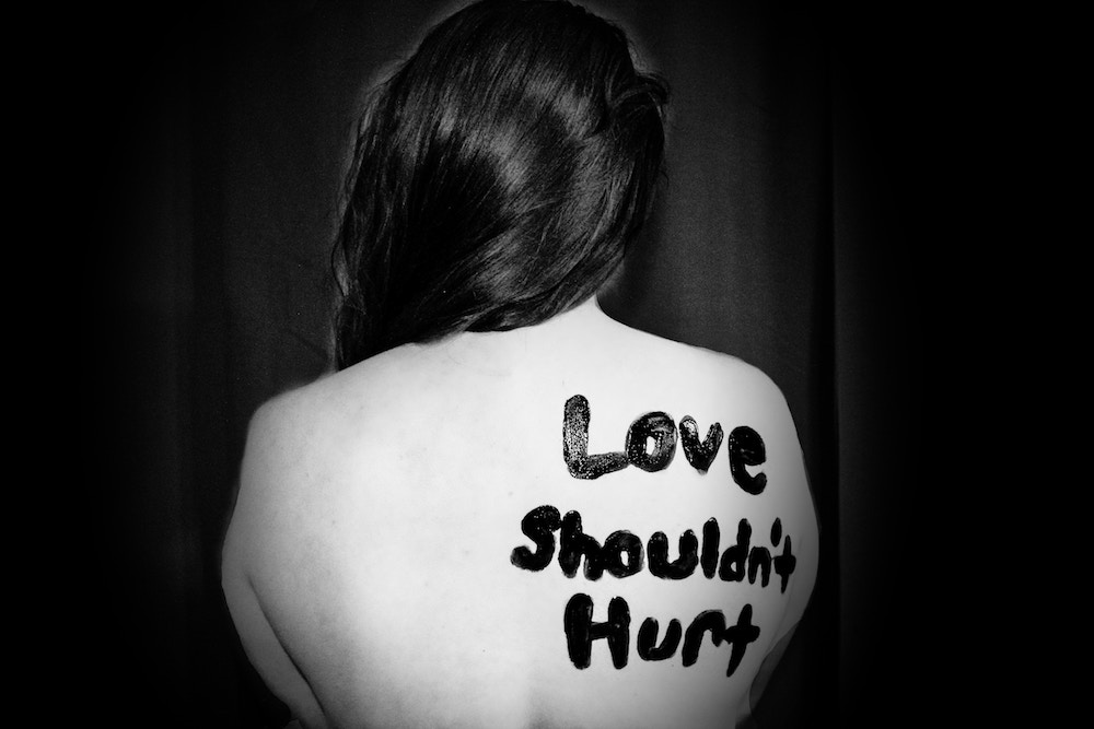 'Love shouldn't hurt' written on woman's back