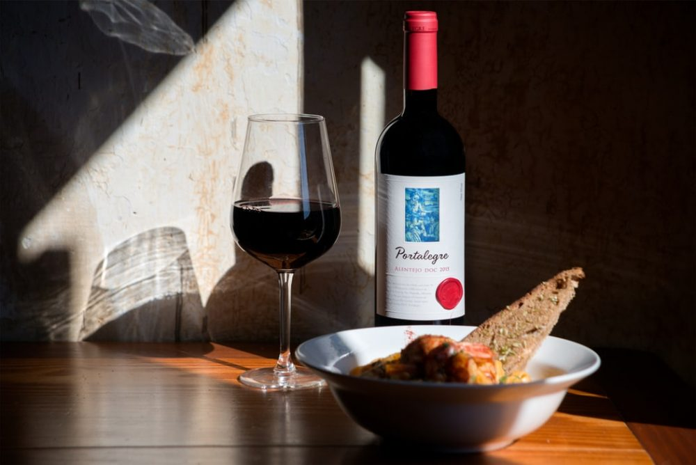 close up of a glass of red wine, bottle and a meal on the table