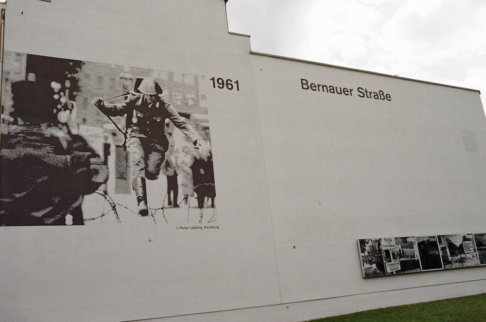 The side of white house, with a black and white image printed onto it of a soldier jumping over the barbed wire wall, next to which it says Bernauer Straße