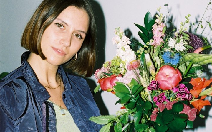 Romy St Clair looking into the camera holding a bright bunch of flowers