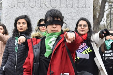 Feminist pointing the finger to the camera in unison during the performance 'Un violador en tu camino' in front of London parliament