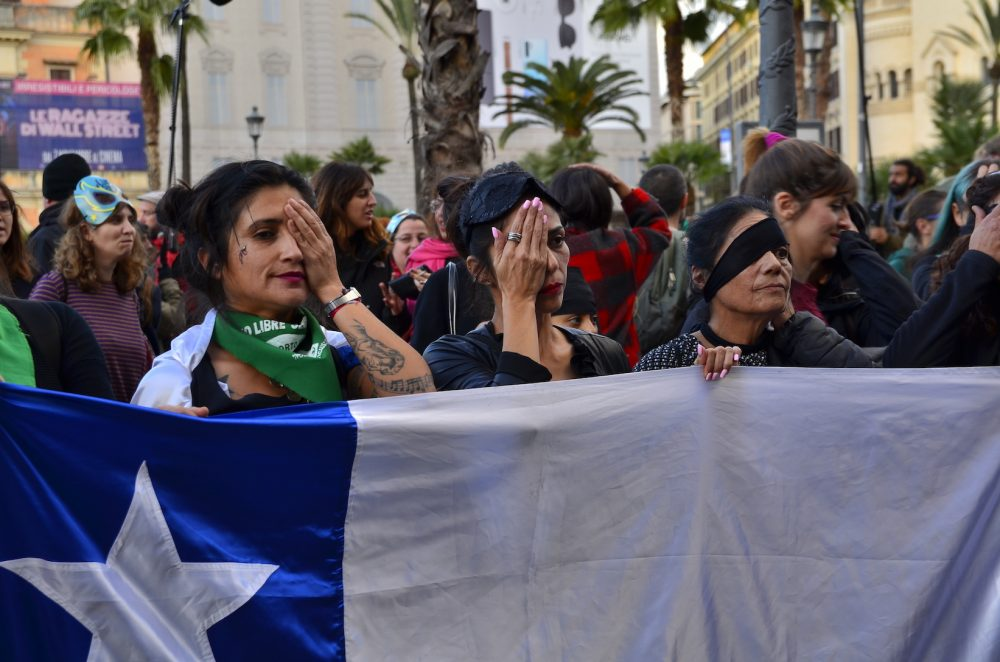 Latin American women holding a Chilean flag and covering their eyes during a feminist protest