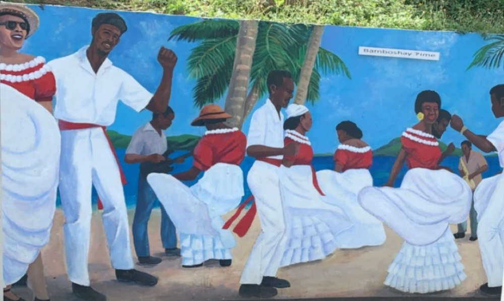 men and women dressed in red and white painted on a wall symbolising the traditional clothing from the British Virgin Islands.