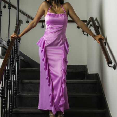 A woman modelling the Pink Frill Siren Dress by Ferf. She stands on a staircase and wears a tight-fitting bright pink halter neck dress with ruffled material coming over the hips and down the skirt of the dress.