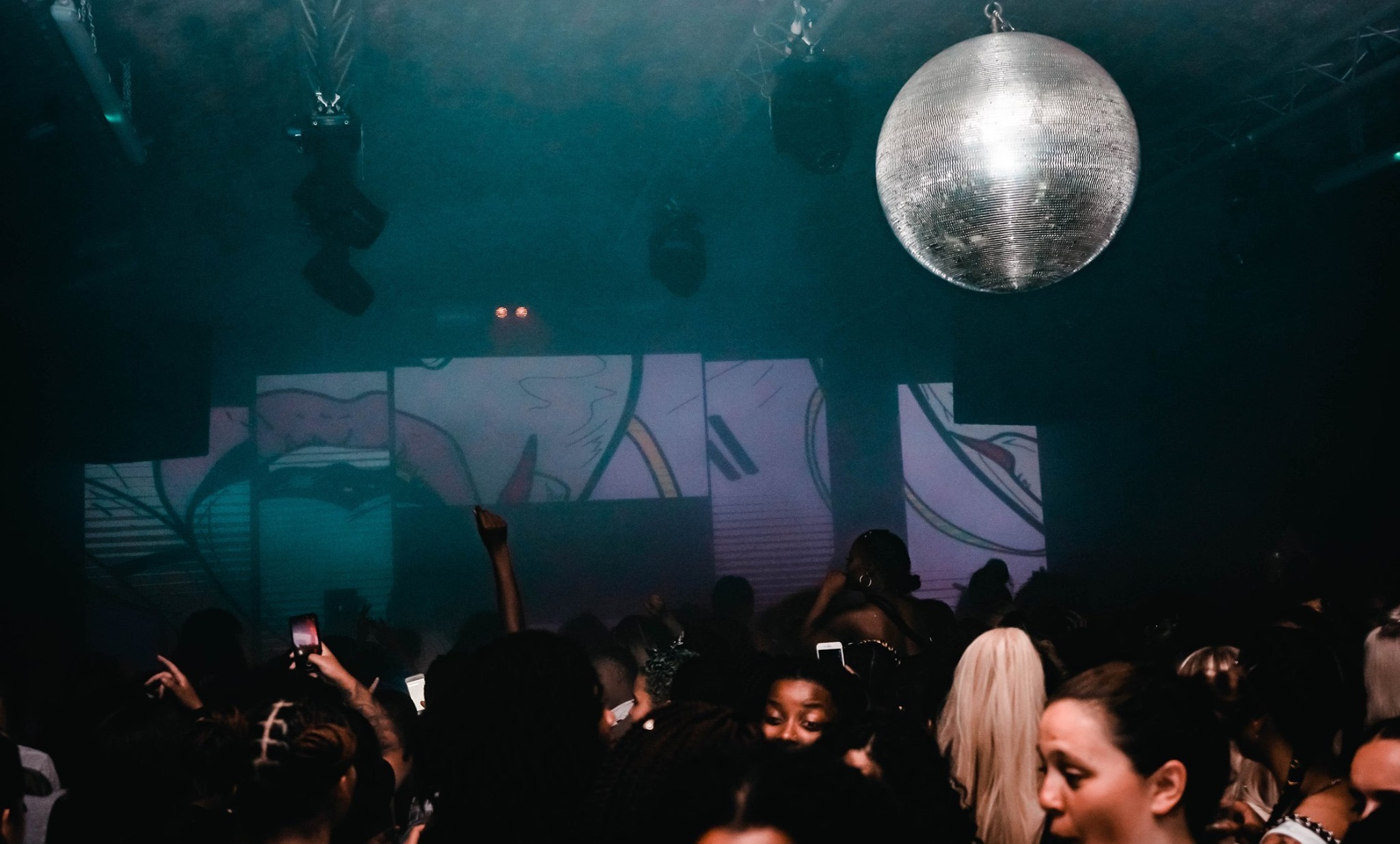 A crowd of women dancing by a disco ball at a night set up by LICK Events