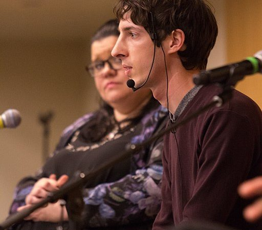 Side profile of James Damore wearing a headset and speaking on a panel at Portland State University