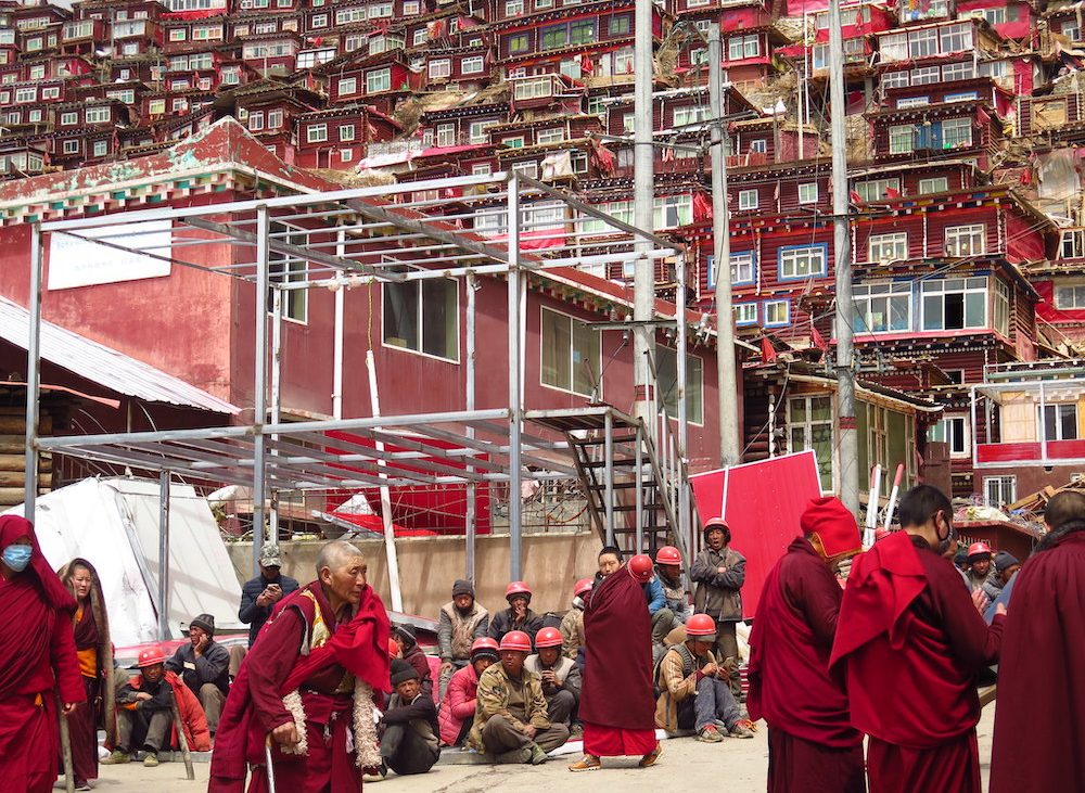 Tibetan monks pass by Chinese workers in Larung Gar