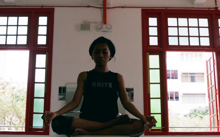An image of one of the performers exhibiting a meditative pose in rehearsal for Luna(s)