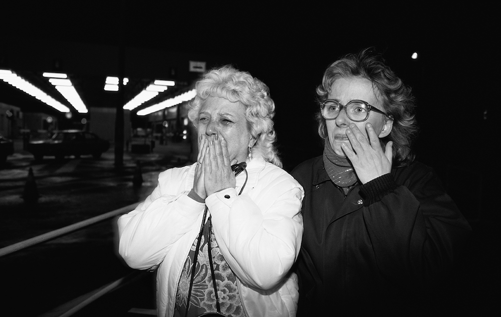 Two women, one with her hands over her mouth the other wiping a tear from her face.
