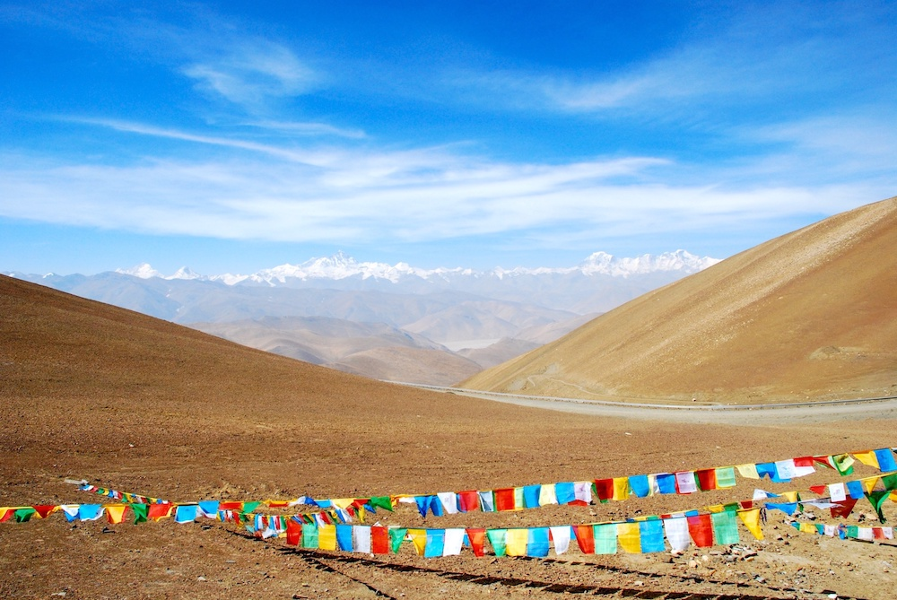A view of the Tibetan Plateau with prayer flags in the foreground and mountains in the distance.