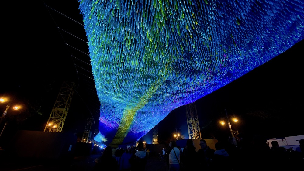 The Visions in Motion installation at night, strips of paper hanging from a net that is illuminated with blue light.