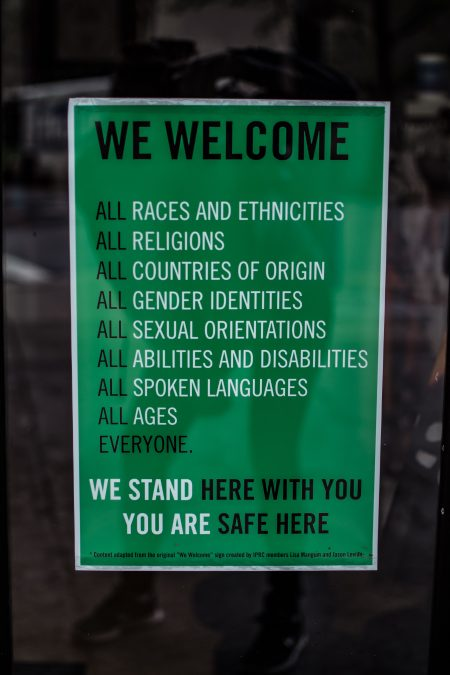 "A poster in a window that details the fact that the place welcomes people of all backgrounds, including race and ethnicity, religion, gender, abilities and ages. It reads at the bottom ""We stand here with you. You are safe here."""