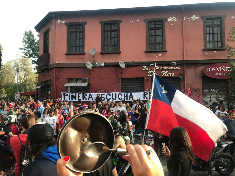 Civil protest in Chile, a group of people can be seen, with flags and instruments, many with their arms held high.