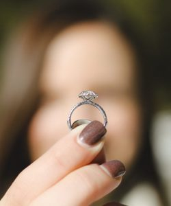 A blurred face of a woman is seen holding a ring