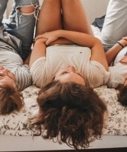 Three young women lying on a bed with their legs in the air, chatting and laughing with each other.
