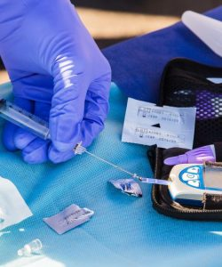 Doctors using a blue glucose machine used for diabetics.