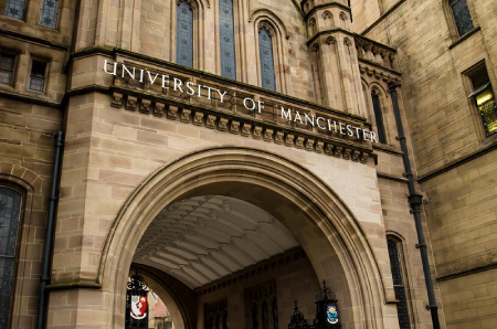 University of Manchester's monumental Gothic entrance. Above the arched portal cast metal letters spell the name of the institution.