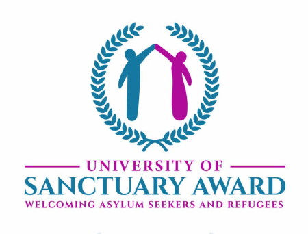 "The official logo of the University of Sanctuary Award: two stylised figures (a man on the left and a woman on the right) hold their hands together and raise them above their heads. Both figures are surrounded by a laurel wreath. Below the latter, there are the following words: ""University of Sanctuary Award: welcoming asylum seekers and refugees."""
