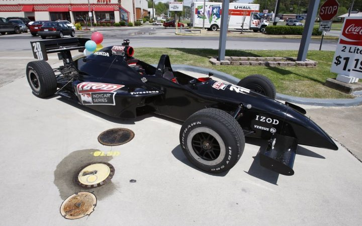 A black Formula One car stands parked at a petrol station.