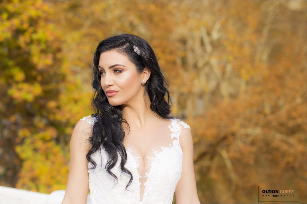 An image of a bride having her picture taken in her wedding dress during the season of autumn.