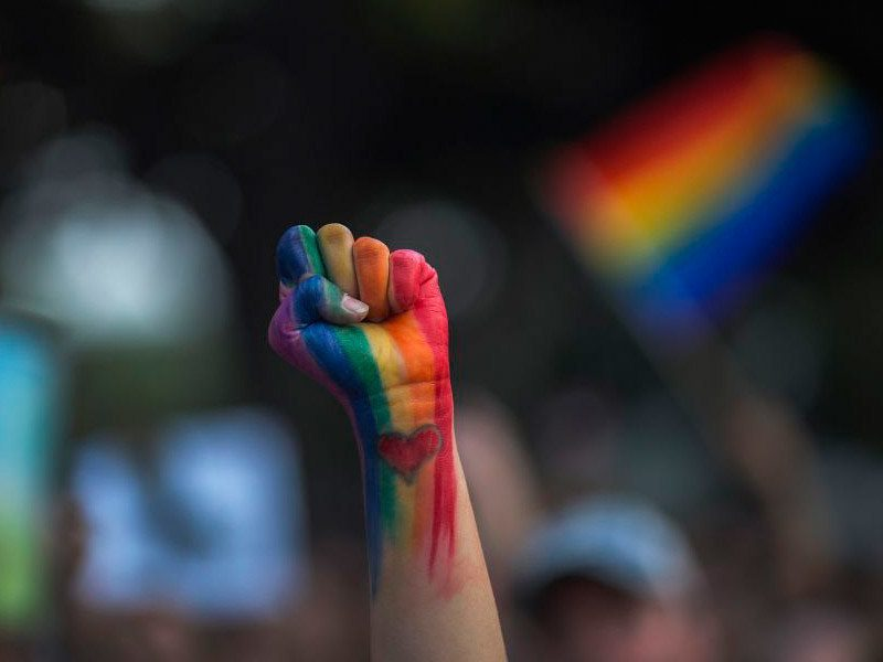 The LGBTQ colours painted on a persons hand with a love heart.