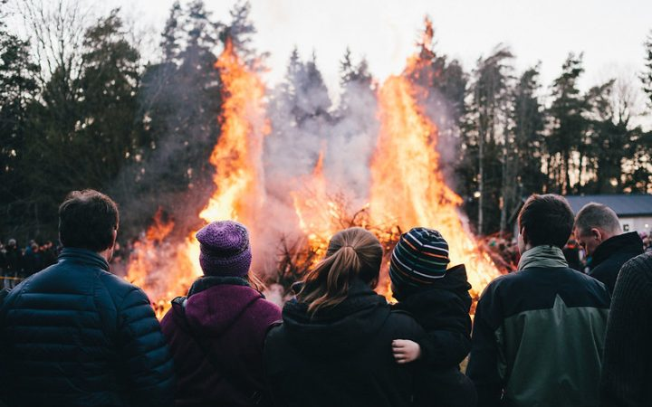 A bonfire on the day of Valborg, a group of people surrounding the fire.