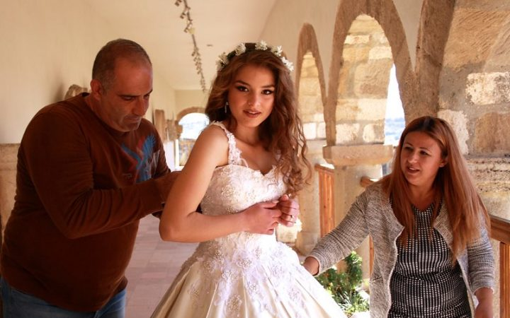 A bride preparing for her wedding with her parents help.