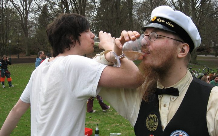 Two guys celebrating Valborg by having a drink in the park.