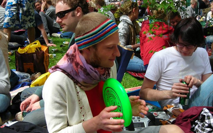 A man enjoying the celebrations of Valborg in the park looking very colourful with a frisbee in his hand.