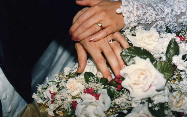 A newly married couple holding hands showing of their wedding rings, placing their hands on top of a bunch of white and green flowers.