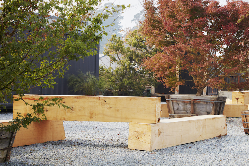 Alongside black shipping container studios, wooden beams and trees in large planters form a modular 'kit' of moving garden parts at a waterfront site.
