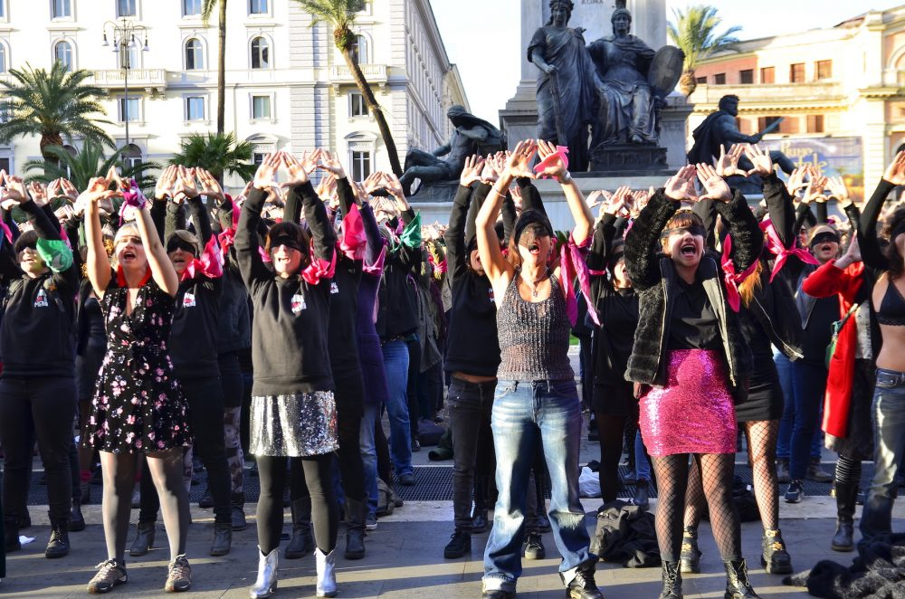 Women performing 'A rapist in your way' in Rome, they are standing in rows with their hands in the air and wearing a blindfold.
