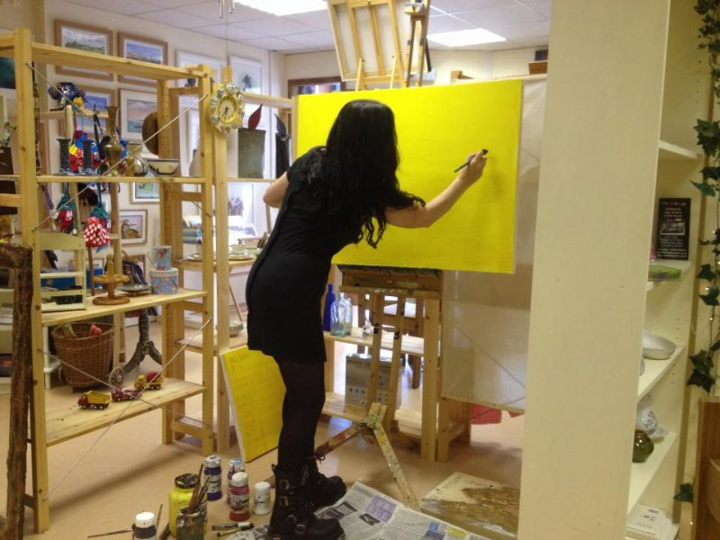 Naomi Walker painting on a yellow canvas in her home.