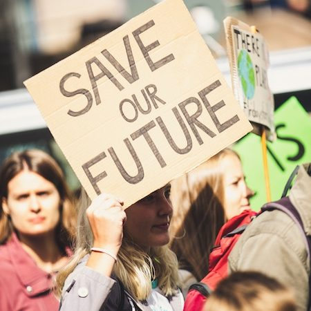 Young girl holding up a sign saying 'save our future' at one of the Fridays for Future protests in Europe.