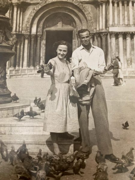 A black and white image of the authors grandparents in Venice. They are surrounded by pigeons in front of the cathedral of Venice.