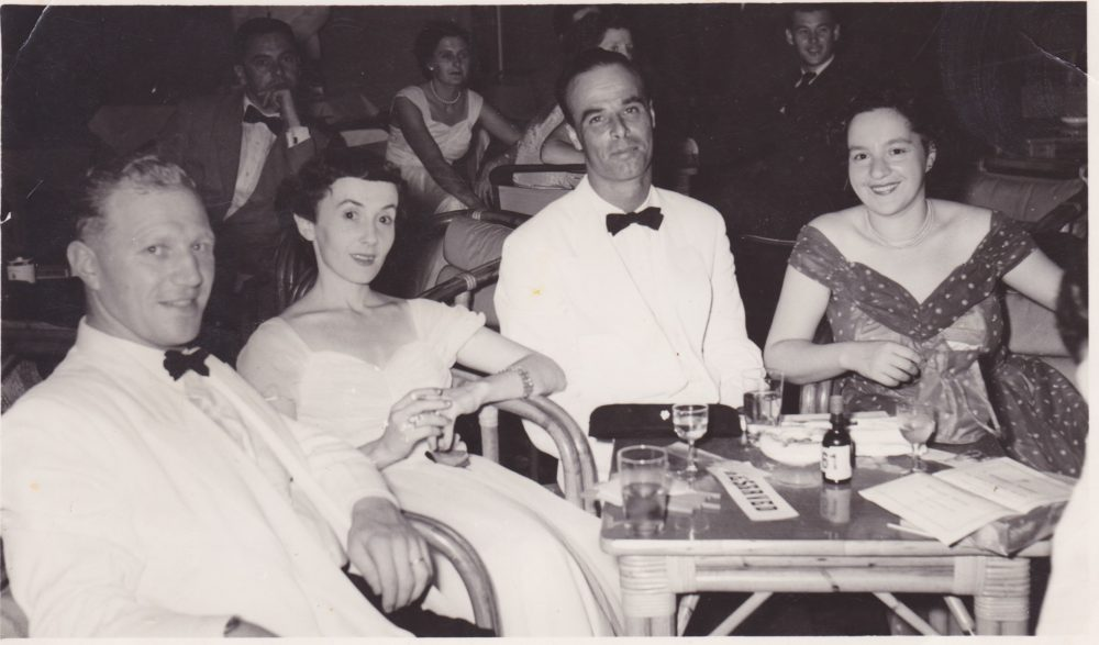 A black and white image of four people sitting at a table. All are wearing evening wear.