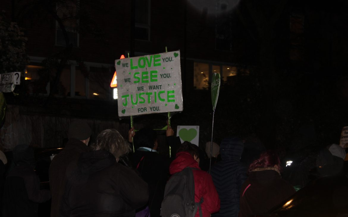 Woman holds sign at Grenfell march reading 'we love you, we see you, we want justice for you'