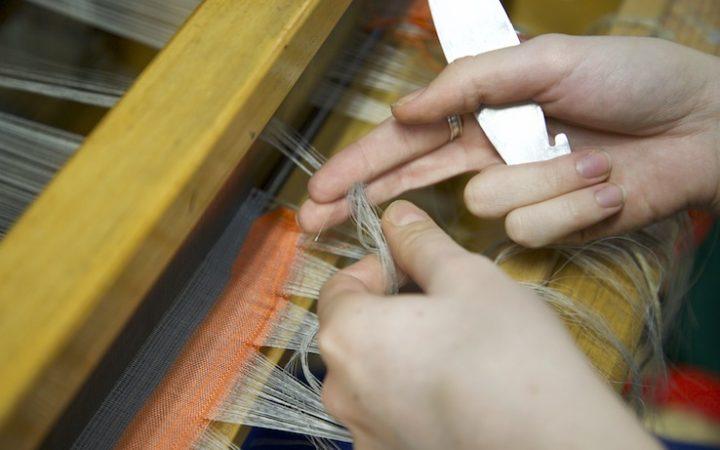 Caitlin preparing to cut thread on loom