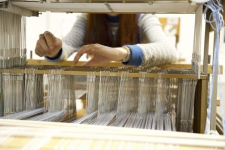 Caitlin's hands hovering over the inside of a loom, fixing any preventable mistakes