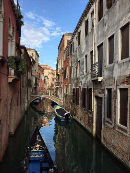 An image of Venice. a canal stretches off surrounded by historical buildings. There are several boats on the water.