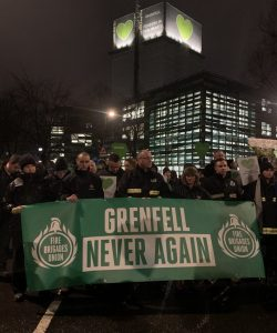 Firefighters hold banner in silent Grenfell march reading 'Grenfell never gain' by the Fire Brigades Union
