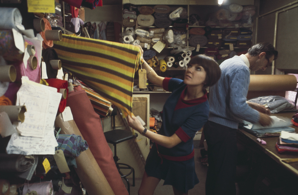 Mary Quant selecting fabric in a fabric shop