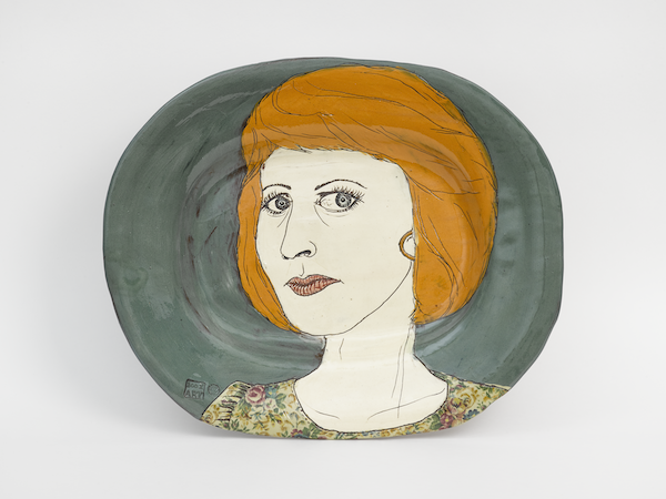 Plate with an illustration with a female 'newsreader' with bright orange hair