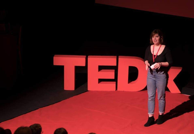 Bethany Dawson a student standing on stage giving a Ted Talk about living with and invisible illness.