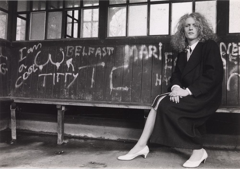 Black and white image of Grayson Perry as a young man dressed a woman, sitting on a bench