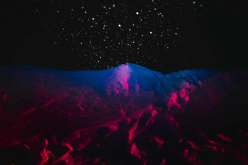 Mountainous terrain and a starry night sky with pink hues