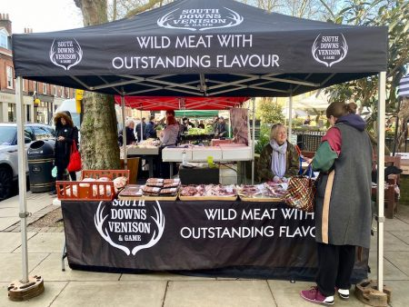 Debbie Smallman sitting at her stall at Pimlico Farmer's Market with an assortment of meat before her, talking to a customer.