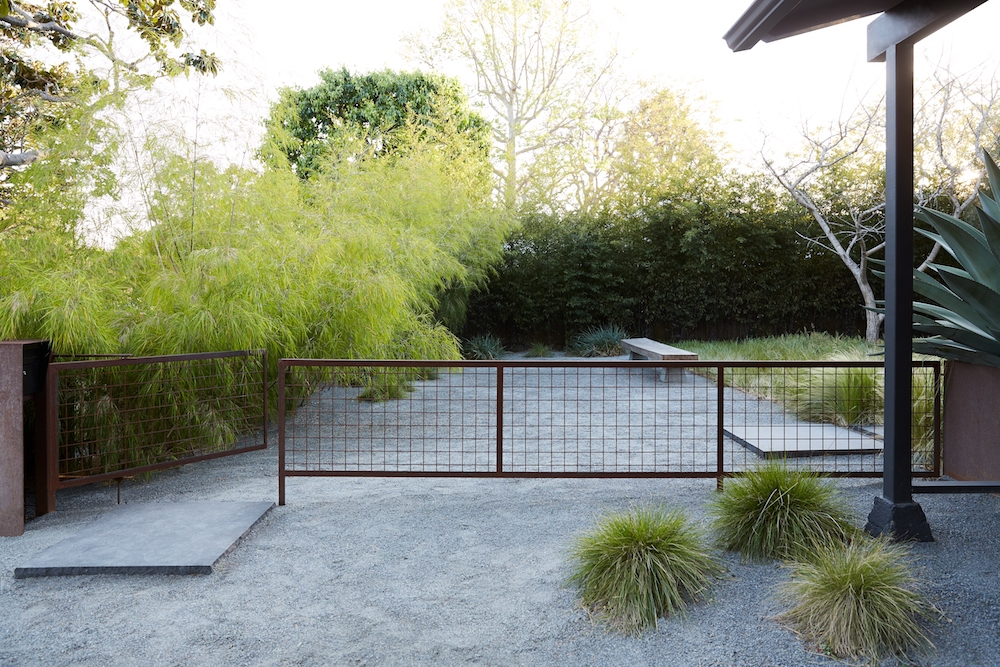A metal gate in the entranceway to Takashi Yanai's black bungalow, accented by Terremoto's planting of Mexican Feather grasses.