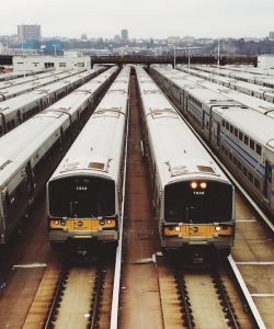 A row of trains waiting at a station alongside each other.