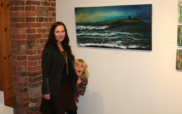 Naomi Walker and Daughter, Ruby at her exhibit. They are standing in front of her painting of an ocean.